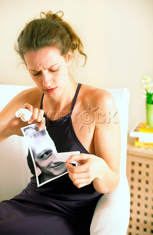 Young woman destroying photo