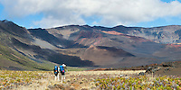 Two male hikers at the base of the crater take a moment to photograph the Sliding Sands trail and visitor center from inside the crater in HALEAKALA NATIONAL PARK on Maui in Hawaii USA