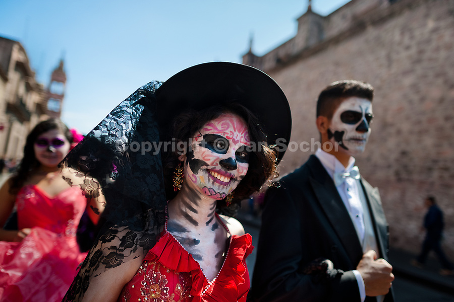 A young couple, costumed as 'La Catrina', a Mexican pop culture icon representing the Death, walks through the town during the Day of the Dead festivities in Morelia, Michoacán, Mexico, 1 November 2014. Day of the Dead ('Día de Muertos') is a syncretic religious holiday, celebrated throughout Mexico, combining the death veneration rituals of the ancient Aztec culture with the Catholic practice. Based on the belief that the souls of the departed may come back to this world on that day, people gather on the gravesites praying, drinking and playing music, to joyfully remember friends or family members who have died and to support their souls on the spiritual journey.