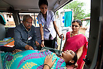 21 May 2013, Mandiganal Village, Karnartaka, India:   Dr Bellada of the Karnataka Mobile Health Clinic project conducts a check up on Savita Mallakarjun Bendigeri, (21) who is due to give birth on June 16, at  Mandiganal Village outside of Hubli. Assisting him is nurse Anita Poojara  (26) and accredited social health activist (ASHA) Renuka  Baramappa who refers patients to the project. The World Bank is financing the Karnataka Health Systems Project that is bringing mobile health clinics to remote villages in Karnataka and covers the cost of an ambulance, a doctor, pharmacist, two nurses, a cleaner and a driver. Villagers have the opportunity to see a doctor once a week for basic services and will be referred to Primary Health Care centres for larger issues Picture by Graham Crouch/World Bank