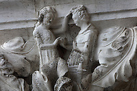 Sculpted capital of a marriage ceremony, carved 1340-1355, thought to be by Filippo Calendario, 1315-55, from Column 24, depicting Phases in Fathering, of the ground floor Piazzetta San Marco columns, on the Doge's Palace or Palazzo Ducale, begun 1340 and built in Venetian Gothic style, Venice, Italy. The palace has 2 arcades with 14th and 15th century capitals and sculptures, and a loggia above with a decorative brickwork facade. It was the residence of the Doge of Venice, the supreme authority of the former Republic of Venice, until the Napoleonic occupation in 1797, and is now a museum. The city of Venice is an archipelago of 117 small islands separated by canals and linked by bridges, in the Venetian Lagoon. The historical centre of Venice is listed as a UNESCO World Heritage Site. Picture by Manuel Cohen