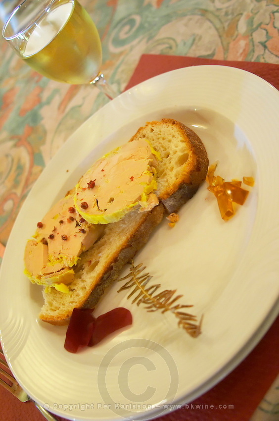 Two big slices of Foie gras duck liver with some rose red pepper on served on a slice of bread with some wine jelly made with sweet white Monbazillac wine Ferme de Biorne duck and fowl farm Dordogne France Workshop on how to make foie gras duck liver pate and other conserves
