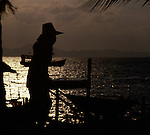Silhouette of Asian worker pushing wheelbarrow,Pattaya, Thailand.