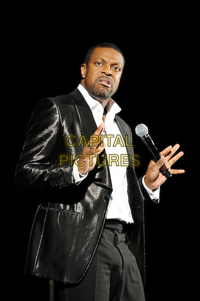 Chris Tucker.Performing his stand up show, Hammersmith Apollo, London, England, UK, 24th November 2012..show on stage comedy half length white shirt black jacket  leather shiny trousers microphone  hands funny mouth expression .CAP/MAR.© Martin Harris/Capital Pictures.
