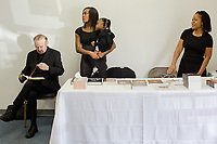 Reverend Bob Larson reads his bible, and Marissa Boone, her daughter Madisyn, 2, and Brittney Linyear (ALL CQ) work the merchandise table at Miracle Life Ministries International Church, a charismatic deliverance church, in Raleigh, NC Sunday, October 15, 2017. (Justin Cook for The Sun)