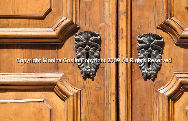 Detail of a door with faces as the key holes in Bologna, Italy.