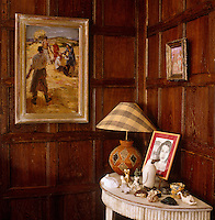 A console table displays a collection of figurines and a framed portrait drawing on an easel whilst an impressionist gilt-framed painting hangs on the ajdacent panelling