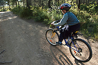 Boy riding his bike along on a dirt road through a forest, Vitrolles, Provence, France.