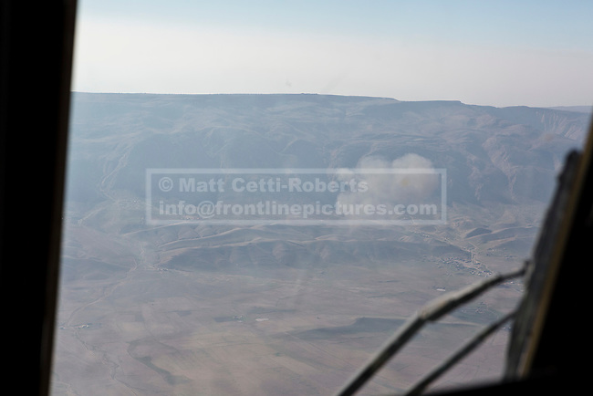 11/12/2014. Sinjar Mountains, Iraq. Smoke rising from the site of a suicide car-bomb attack at the base of Mount Sinjar Mount Sinjar is seen through the cockpit windows of an Iraqi Air Force Mi-171E Hip helicopter during a mission to supply Yazidi refugees on the 75 mile long ridge-line. <br /> <br /> Although a well publicised exodus of Yazidi refugees took place from Mount Sinjar in August 2014 many still remain on top of the 75 km long ridge-line, with estimates varying from 2000-8000 people, after a corridor kept open by Syrian-Kurdish YPG fighters collapsed during an Islamic State offensive. The mountain is now surrounded on all sides with winter closing in, the only chance of escape or supply being by Iraqi Air Force helicopters.