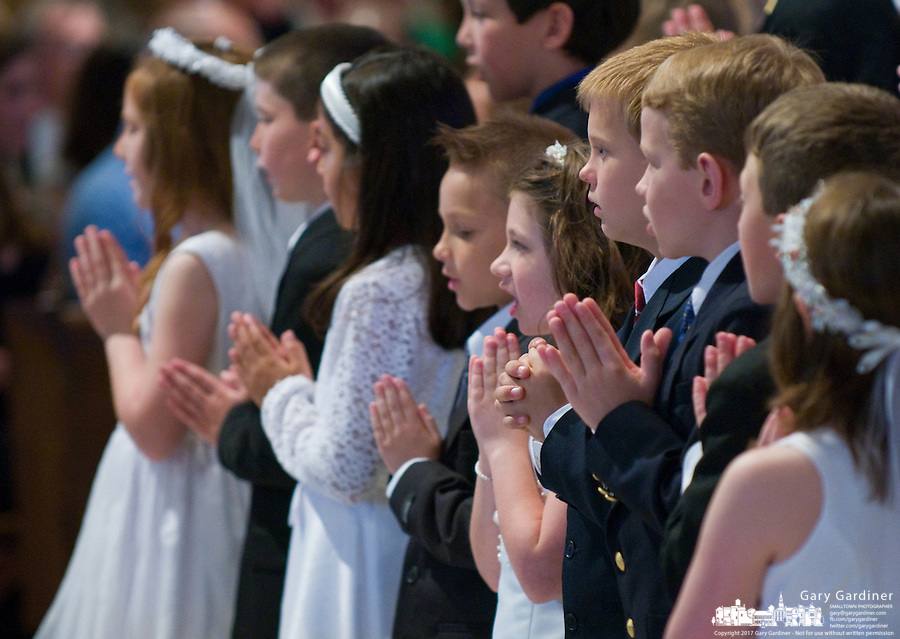 Children stand in their church best with folded in prayer during First Communion services at a Catholic church.  Photo Copyright Gary Gardiner. Not be used without written permission detailing exact usage.