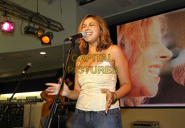 CHARLOTTE CHURCH.Performs live at HMV during a instore gig and signing session, HMV Oxford Street, London,.July 12th 2005..half length hands yellow striped vest top funny face eyes shut closed.Ref: HT.www.capitalpictures.com.sales@capitalpictures.com.©Hugh Thompson/Capital Pictures