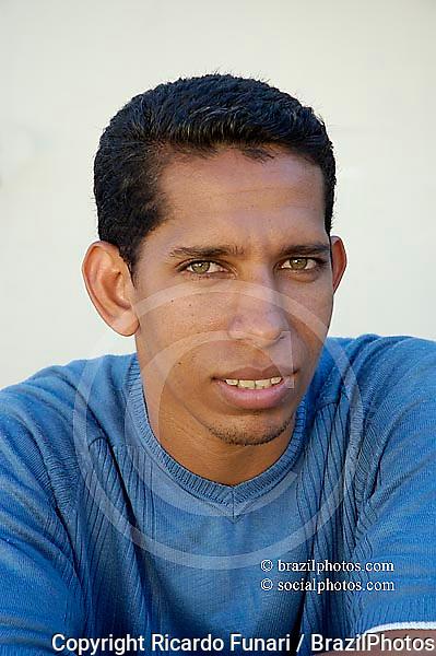 Portray of racial-mixed young brazilian man. Green eyes.