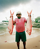 CAYMAN ISLANDS, Grand Cayman, fisherman holding two red snapper caught in the Caribbean Sea