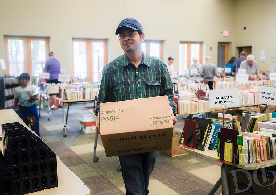 NWA Democrat-Gazette/CHARLIE KAIJO Bipin Jadhav of Bentonville carries a box of books he bought during a book sale, Thursday, October 4, 2018 at the Bentonville Public Library in Bentonville.<br /><br />Friends of the Bentonville Library held a soft opening for their annual fall book sale. Members enjoyed early access to the sale. The sale will go until Saturday from 10am to 4pm at the Walmart community room.