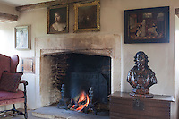 In the living room an antique bust of an aristocrat takes pride of place on a wooden chest next to the blazing log fire in the large stone fireplace