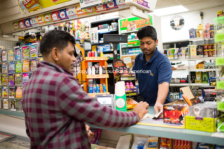 WATERBURY, CT- 7 January 2015-010716EC09-   Emran Ahamath sells a Powerball ticket to Tuam Harries Thursday night at the Quik Mart at 990 Huntington Ave in Waterbury.  Over 200 tickets were sold at the gas station in one day, a huge jump in daily sales now that the jackpot is around 700 million dollars. Harries, the customer, says if he wins, he will keep one million dollars and give the rest to charity. Erin Covey Republican-American