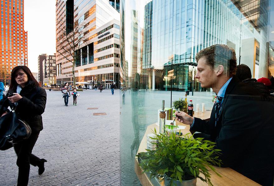 Nederland, Amsterdam, 5 maart 2013<br /> Zuid-as. Zakencentrum van Amsterdam met hoofdkantoren en advokatenkantoren etc etc.<br /> Man zit voor het raam te eten bij eettentje van Julia's.<br /> Foto(c): Michiel Wijnbergh