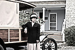 A lady standing next to a 1912 truck in her driveway of her house