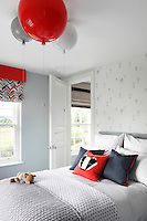 Cheerful red soft furnishings and light fittings enliven the pale colours of this child's bedroom