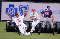 Members of the Rome Braves, including Cory Brownsten (30), right, and Greenville Drive, including Boss Moanaroa (29), left, and Matt Marquis (23), center, stage a mock battle, attacking from opposite sides of the field, during a lengthy rain delay before a game on July 5, 2012, at Fluor Field at the West End in Greenville, South Carolina. (Tom Priddy/Four Seam Images)