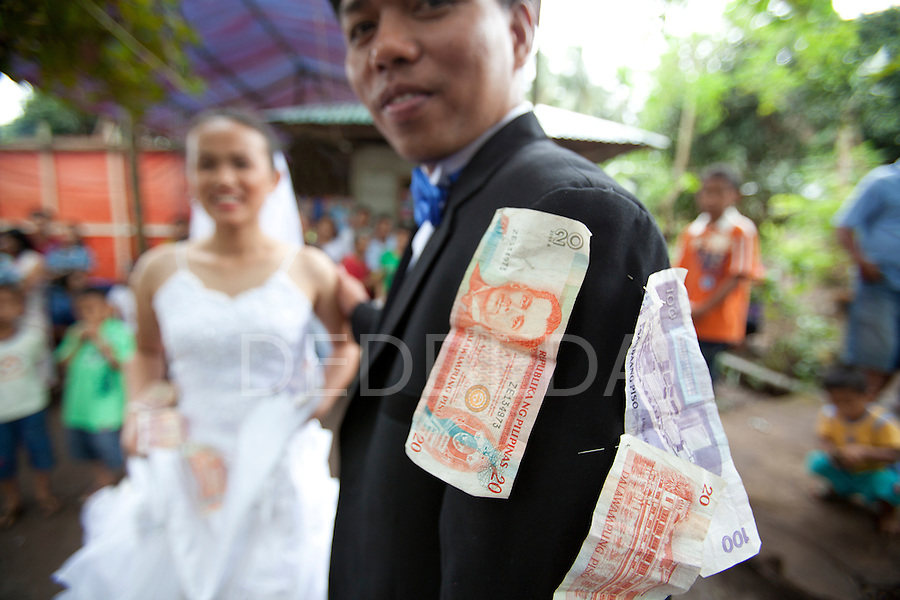 A bride and groom celebrate on their wedding day at an outdoor reception in a rural area near San Jose, Negros Oriental, Philippines. One Filipino tradition is that people pin money on the bride and groom in exchange for a dance.