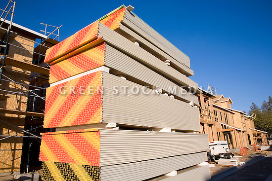 A low angle view of a colorful stack of Pabco gypsum wallboard at the real estate developer D. R. Horton's 181-unit housing development called Arbor Real. The project under construction consists of luxury townhouses and condominiums on the site of the former Rickey's Hyatt adjacent to El Camino Real. Palo Alto, California, USA