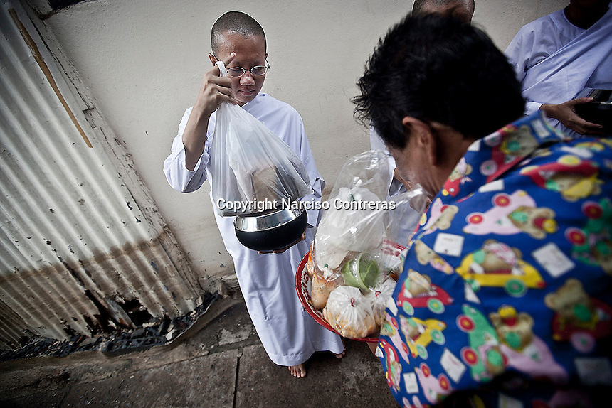"A Buddhist woman offers charity to Thai nuns clad in white robes at the streets as they stand silently in the early morning holding out their alms bowls hoping for food or monetary offerings. Vanished by centuries the lineage of ""Bhikkhu?nii"" (Order of Nuns) has been brought to the ongoing Thai society's debate. White-clad thai nuns, who keep the eight precepts and have their heads and eyebrows shaved are known as the lon-existing ""mae chees"" (low category to call the lay nuns). Females who have turned to religous life, as renunciants, live ostracized and marginalized by the Sangha (Buddhist community) and Thai society, denying them full access to the monastic life as well as rights and support from the government. Today nunhood is not recognized by any asian country belong to the Theravada Buddhist order. Most of the eight precept holders live in temples run by male abbots, at the shadow of the monks; with the exceptional existence of a few para-monastic institutions as the Sathira Dhammasathan meditation centre, where ""mae chees"" are not allow to held a temple, but not denied to practice the spiritual life."