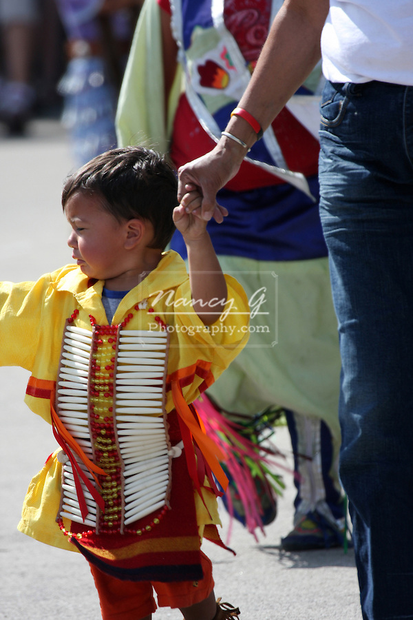 A young Native American boy dressed to dance at a Pow Wow at the Milwaukee Lakefront Indian Summer Festival, Wisconsin, while walking with his mom