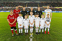 Referee Neil Swarbrick (C) with Emre Can of Liverpool (L) and Federico Fernandez of Swansea City (R) and children mascots during the Premier League match between Swansea City and Liverpool at The Liberty Stadium, Swansea, Wales, UK. Monday 22 January 2018
