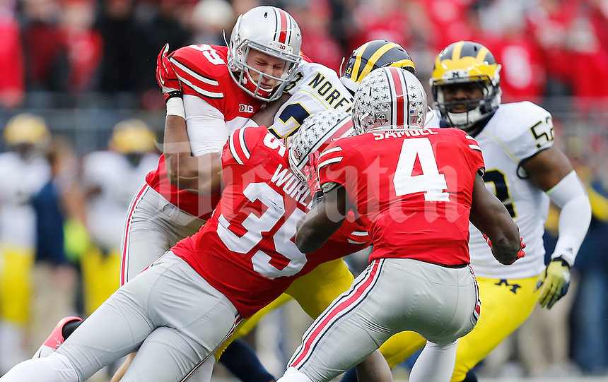 Ohio State Buckeyes place kicker Kyle Clinton (39) and Ohio State Buckeyes safety Chris Worley (35) tackle Michigan Wolverines wide receiver Dennis Norfleet (23) as he returns a kick during the college football game between the Ohio State Buckeyes and the Michigan Wolverines at Ohio Stadium in Columbus, Saturday morning, November 29, 2014. The Ohio State Buckeyes defeated the Michigan Wolverines 42 - 28. (The Columbus Dispatch / Eamon Queeney)