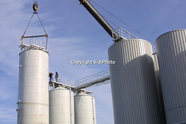 Foto: VidiPhoto..DODEWAARD - Bij het Riho in Dodewaard, een opslagbedrijf voor veevoedergrondstoffen, zijn vrijdagmiddag met een hoogwerker vier silo's van 15 meter hoog verplaatst naar de achterzijde van het bedrijf. In totaal staan er 52 silo's van ongeveer gelijke hoogte. Hoewel alle tanks op hetzelfde terrein staan, vielen deze vier, enkele meters buiten het bestemmingsplan. Dus moesten ze op straffe van een dwangsom van 10.000 gulden per dag verplaatst worden. Riho probeert de bedrijfsschade nu te verhalen op de gemeente via een bodemprocedure bij de Raad van State.