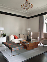 The suite living room is furnished with a tufted Bentley leather sofa and a pair of wing-backed armchairs, complemented with a leather upholstered bench and a menswear inspired herringbone rug with seatbelt detailing
