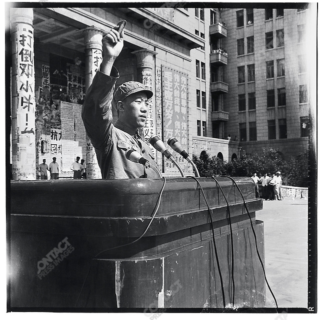 """PLA member Zhang Chunyu addresses a crowd gathered in front of the North Plaza Hotel to commemorate the one-year anniversary of Mao Zedong's """"Bombard the Headquarters"""" big character poster, which precipitated the Chairman's attack on the Party establishment at the start of the Cultural Revolution. The banner reads, """"Down with Liu Shaoqi and Deng Xiaoping."""" Harbin, 5 August 1967"""