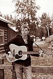USA, Alaska, Talkeetna, a young man Ian Merkley plays the guitar on the street in town (B&W)