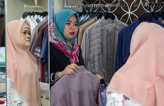 23 JAN, 2018, Jakarta, Indonesia: Shapiro fashion shop sales assistant ,Yani shows off some items to customer Hayu Wulandari. The rise of Islamic fashion is bringing massive revenue boosts to the sector and to the Indonesian economy and individual designers and fashion industry as a whole. Pictured in Jakarta by Graham Crouch for Luzerner Zeitung