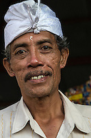 Bali, Indonesia.  Middle-aged Balinese Hindu Man Wearing an Udeng, the traditional Balinese male head cloth. Note how the corner of his right eye-tooth has been filed off, a Balinese custom.
