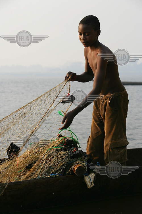Young fisherman with nets in a pirogue - dug out wooden canoe.