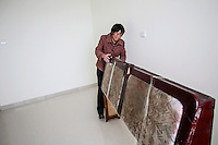 50 year old Chen Hua moves into her new urban home in Liaocheng city in the northeastern Chinese province of Shangdong. Her former village house was bulldozed by the government three years ago to make way for high-rise development. In the four years between her rural home being razed and the completion of her new city apartment, she and her family lived in temporary village housing such as this one. The Chinese government plans to move 250 million rural residents into urban areas over the coming dozen years though it is unclear whether people want to move and where the money for this project will come from. Further urbanisation is meant to drive up consumption to counterbalance an export orientated economy and end subsistence farming but the drive to get people off the land is causing tens of thousands of protests each year. /Felix Features