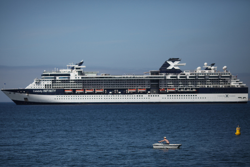 A man rows a boat through Wharf 2 in Monterey while a cruise ship looms in the background on May 13, 2016.