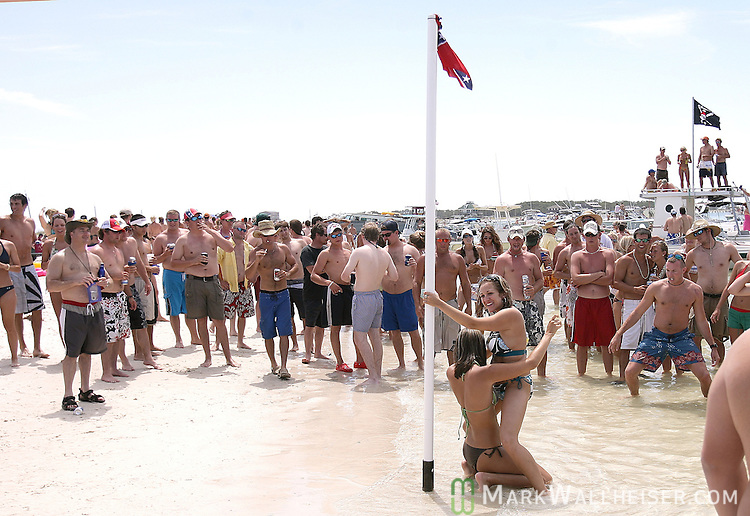 Memorial Day weekend celebrants watch two girls pole dancing on a Confederate flag adorned stripper pole that was erected in the surf at Dog Island for the weekend long White Trash Bash at the remote island off the coast of Carrabelle, FloridaMay 27, 2007.