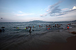 Swimmers enjoy the beach as the sun begins to set in Nha Trang, Vietnam. July 8, 2011.