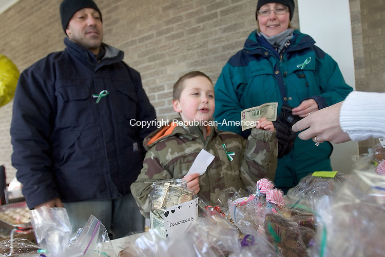 SOUTHBURY, CT. 02 February 2013-020213SV09-Jack Canalori, age 6, takes money while selling baked goods during a baked sale to benefit the Sandy Hook School Support Fund and victims of Hurricane Sandy in Southbury Saturday. Jack along with his mom, Liisa, and dad, Joseph, sold items outside Kmart in the Southbury Plaza. He organized the bake sale himself because he was so upset with the hurricane and shooting at Sandy Hook Elementary School. .Steven Valenti Republican-American.Liisa Canalon (cq)