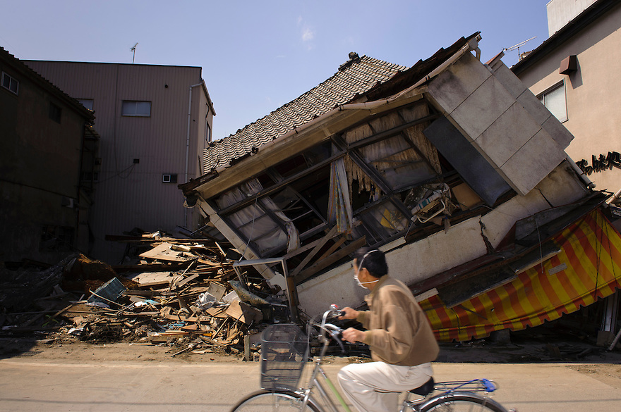 A man on a bicycle passes buildings damaged by the March 11 tsunami, Ishinomaki, Miyagi Prefecture, Japan, May 5, 2011. Almost two months after the devastating earthquake and tsunami the reconstruction has barely begun.