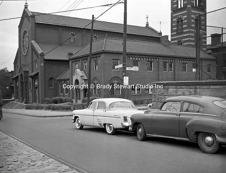 Lawrenceville section of Pittsburgh:  View of the St John the Baptist Church on Liberty Avenue and 36th Street in Lawrenceville - 1957.  Founded in 1878, this Catholic Church served the Lawrenceville area of Pittsburgh. It.steadily expanded until the early 1900's. The church survived a fire, flooding, and the depression..By the late 1950's when steel mills started to close, the.Lawrenceville population declined, much like the rest.of Pittsburgh. Major parishes, including St. John the Baptist, began to lose members. Due to financial and organizational circumstances, the Diocese of Pittsburgh restructured the churches in its jurisdiction in 1993 and St. John the Baptist was closed. Brew Works purchased the building in 1995 and developed it into a restaurant and brew pub. The Church Brew Works opened for business on August 1, 1996.