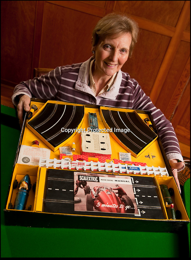 BNPS.co.uk (01202 558833)<br /> Pic: PhilYeomans/BNPS<br /> <br /> Diane Francis with the original Scalextric.<br /> <br /> Blast from the past - 56 year old box of the very first Scalextric finally handed over to inventors daughters.<br /> <br /> The dying wish of Scalextric inventor Freddie Francis has been granted - after his daughters were gifted an original mint set that has been in storage for the past 50 years.<br /> <br /> Freddie and his widow Diane boxed up the original set shortly before he died in 1998 and Diana has waited till now before handing the valuable heirloom over.<br /> <br /> The previously unopened set has been preserved in a wooden box at the Francis family home until now.<br /> <br /> The historic set contains 1950's Ferrari and Maserati style racing car's that would have been driven by Fangio and Stirling Moss and even includes oil to keep the cars running and silicone for 'skid patches'.<br /> <br /> Although the set cost £5 in 1957, it's worth well over £1500 today.