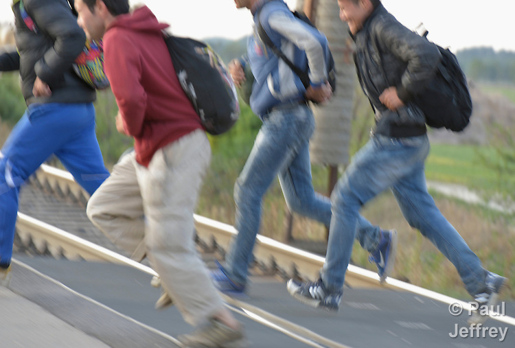 Refugees run across the border into Austria near the Hungarian town of Hegyeshalom. Hundreds of thousands of refugees and migrants flowed through Hungary in 2015, on their way to western Europe from Syria, Iraq and other countries.