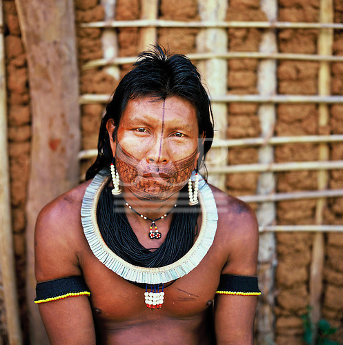 A-Ukre Village, Xingu, Brazil. Kryt, a Kayapo man, in front of a wattle and daub house.