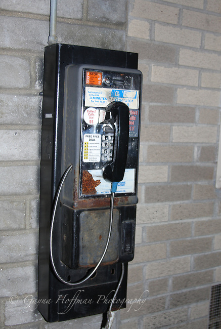 Worn looking pay phone on brick wall.
