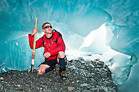 Glacier guide admiring an ice cave on Franz Josef Glacier - Westland National Park, West Coast, New Zealand