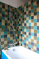 The choice of colours for the tiles that have been laid in a mosaic pattern on the walls of this small bathroom echoes the colours used in the decoration of the whole house